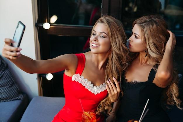 Duas mulheres atraentes tomando selfie juntos