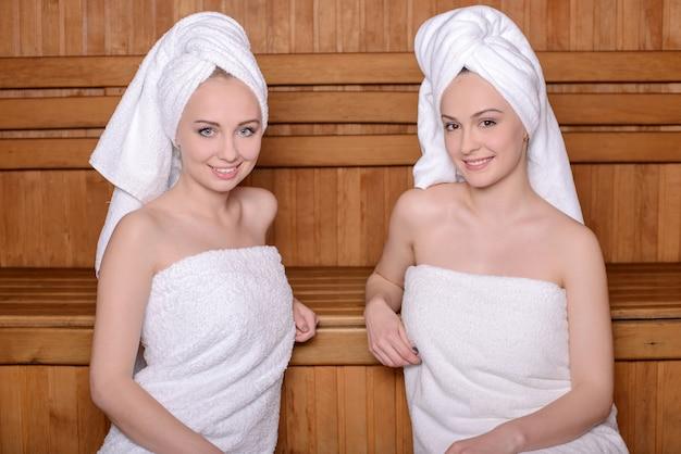 Duas mulheres atrativas envolvidas na toalha que relaxam na sauna.