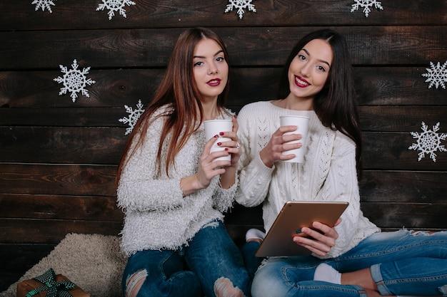 Duas mulheres bebem uma bebida quente e assistem a algo em um tablet