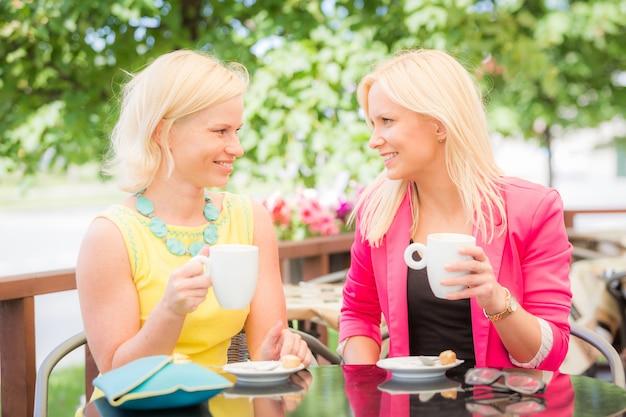 Duas mulheres bonitas, bebendo café no bar