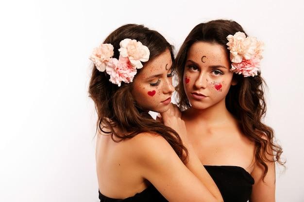 Duas mulheres bonitas com cabelos morenos, flores cor de rosa em seus cabelos e pinturas no rosto parecem gêmeos