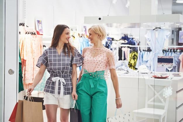 Duas mulheres bonitas com sacos olhando um ao outro com sorriso enquanto caminhava na loja de roupas