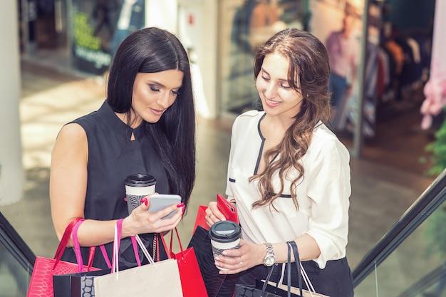 Duas mulheres bonitas com smartphones e sacolas de compras no shopping.