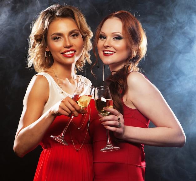 Duas mulheres bonitas com taças de vinho