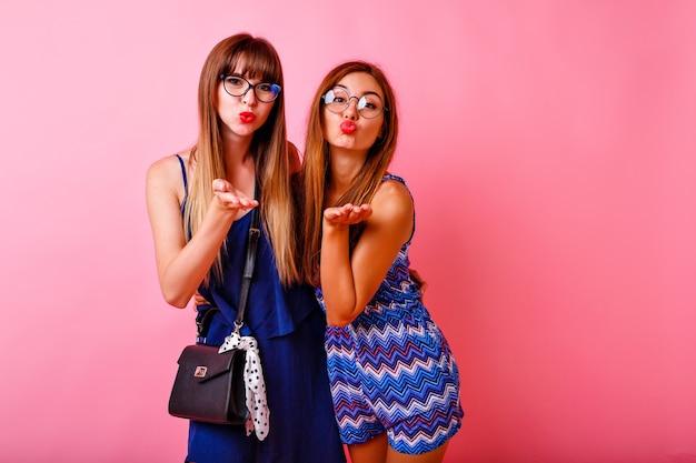 Duas mulheres bonitas e animadas posando de rosa