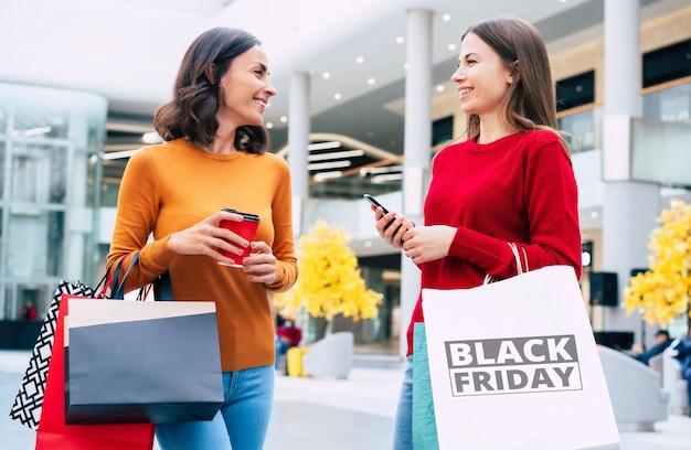 Duas mulheres bonitas e elegantes com sacolas de compras estão passeando no shopping durante a liquidação da sexta-feira negra