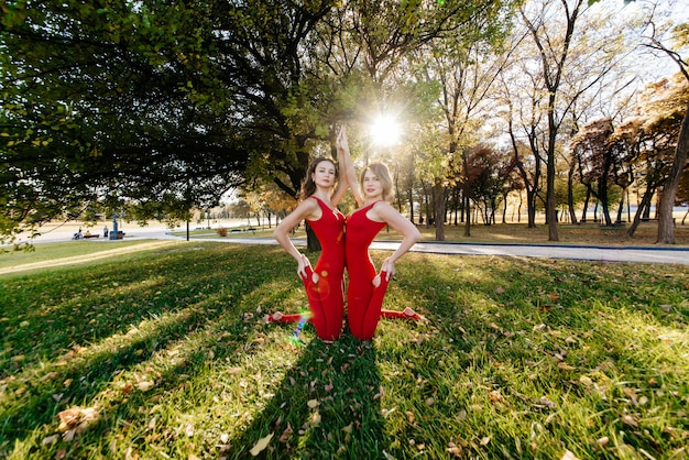 Duas mulheres bonitas e felizes fazendo exercícios de ioga e no parque em um dia ensolarado em close-up