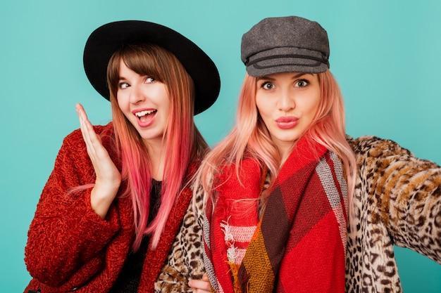Duas mulheres bonitas em elegantes casacos de peles artificiais e cachecol de lã, posando na parede turquesa