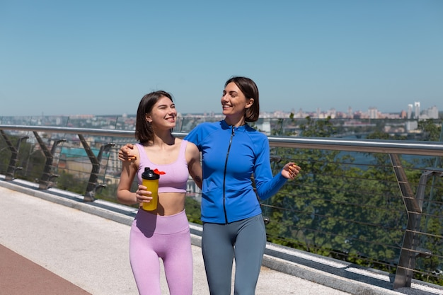 Duas mulheres bonitas em roupas esportivas na ponte amigos felizes e positivos conversam enquanto caminham sorriem, desfrutando de fitness matinal, vista incrível da cidade