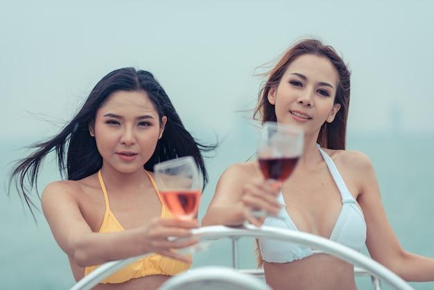 Duas mulheres bonitas em um biquini estão sorvendo o vinho em um iate.
