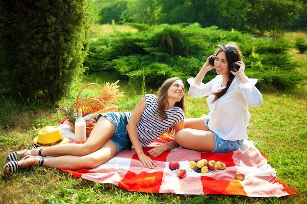 Duas mulheres bonitas em um piquenique, ouvindo música em fones de ouvido