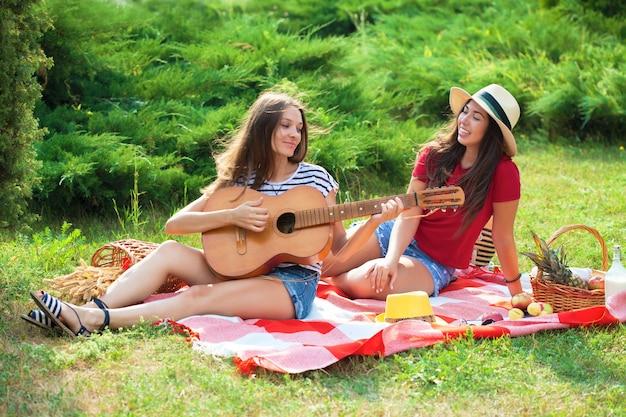 Duas mulheres bonitas em um piquenique tocando violão e se divertindo
