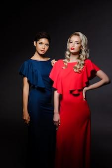 Duas mulheres bonitas em vestidos de noite posando