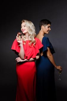 Duas mulheres bonitas em vestidos de noite, sorrindo, segurando copo de champanhe