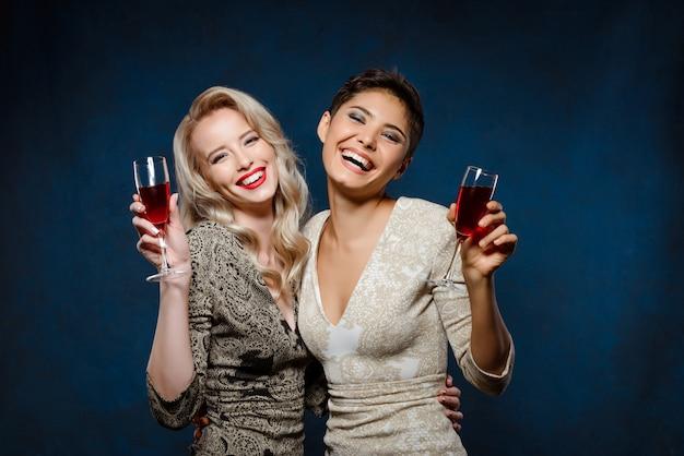 Duas mulheres bonitas em vestidos de noite, sorrindo, segurando copos de vinho