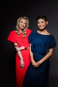 Duas mulheres bonitas em vestidos de noite sorrindo