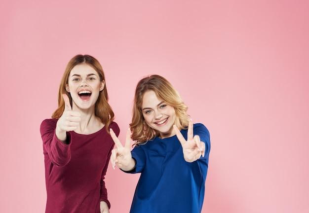 Duas mulheres bonitas estilo elegante comunicação estilo de vida mais divertido fundo rosa