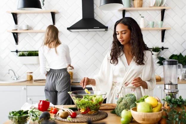 Duas mulheres bonitas na cozinha moderna branca estão fazendo café da manhã saudável