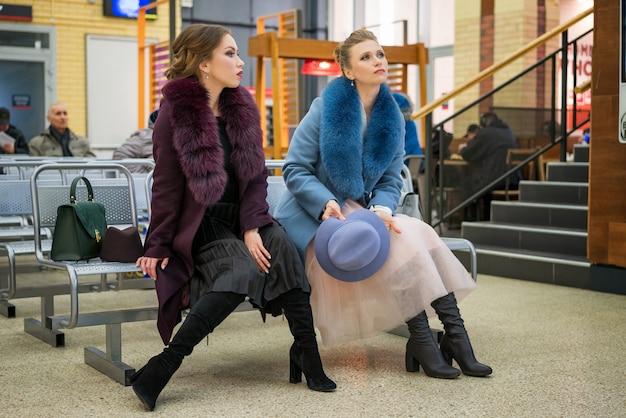 Duas mulheres bonitas na estação esperando o trem
