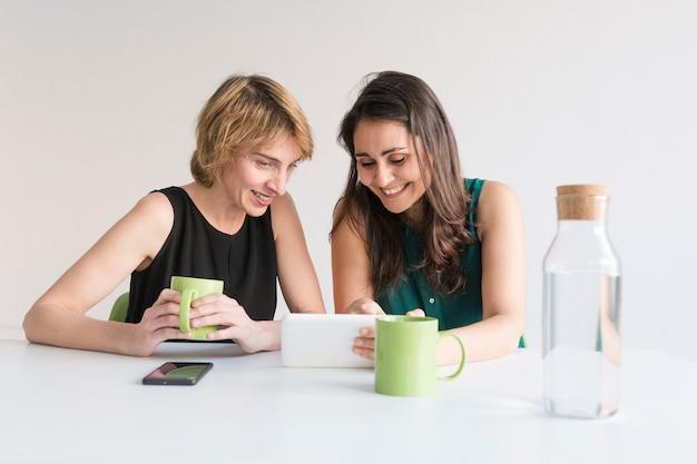 Duas mulheres bonitas no escritório à procura de informações no tablet ou telefone celular. fundo branco. conceito de escritório moderno. jarro de água em cima da mesa.