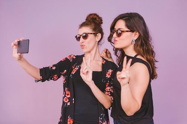 Duas mulheres bonitas se divertindo tomando uma selfie com telefone móvel. dentro de casa. fundo roxo. roupa casual. diversão, felicidade e estilo de vida. óculos de sol modernos