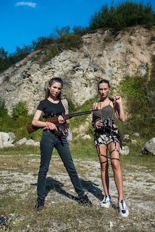 Duas mulheres bonitas sexy com armas de fogo na natureza. aventura