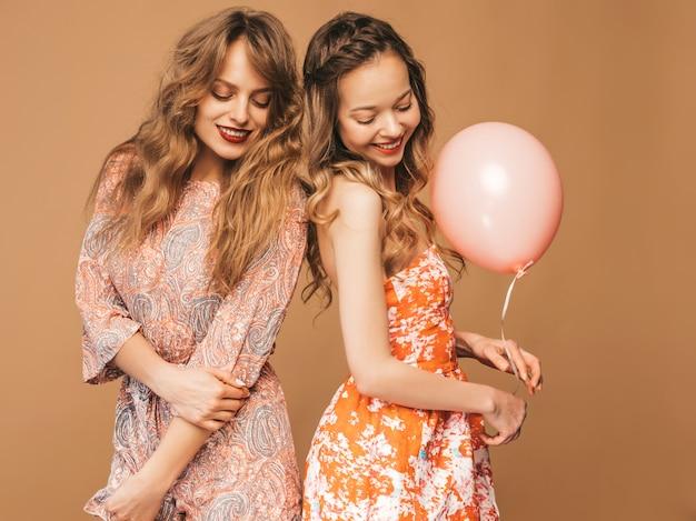 Duas mulheres bonitas sorridentes em vestidos de verão. meninas posando. modelos com balões coloridos. se divertindo, pronto para comemorar aniversário ou festa natalícia