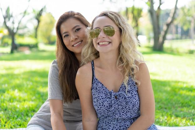 Duas mulheres bonitas sorridentes posando no parque