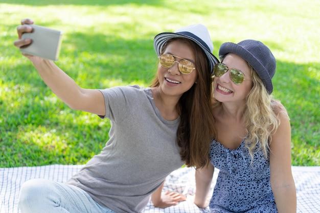 Duas mulheres bonitas sorridentes tirando foto de selfie no parque