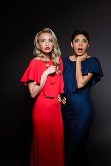 Duas mulheres bonitas surpresas em vestidos de noite