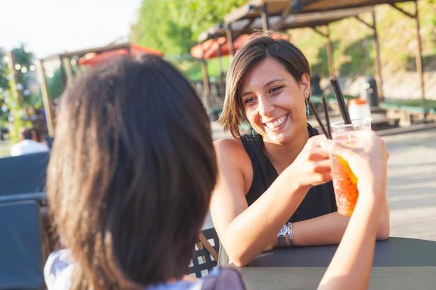 Duas mulheres bonitas, tendo um coquetel ao ar livre ao pôr do sol