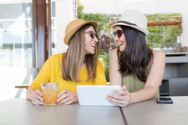 Duas mulheres bonitas tomando café da manhã em um restaurante. eles estão rindo e procurando informações em um tablet. estilo de vida dentro e conceito de amizade