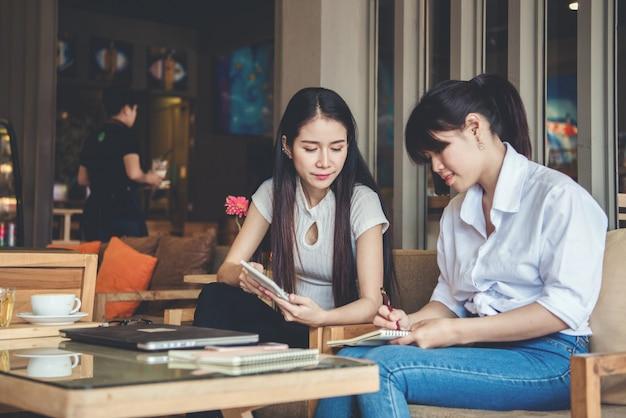 Duas mulheres bonitas, trabalhando em uma loja de café