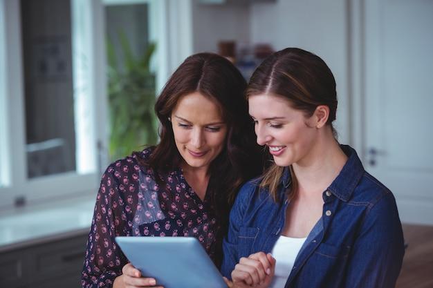 Duas mulheres bonitas usando tablet digital na cozinha