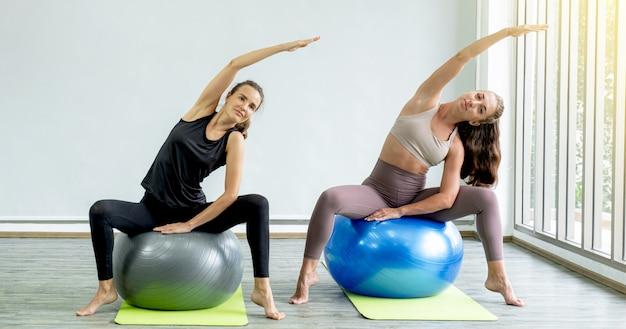 Duas mulheres brancas se exercitando fazendo pose de ioga alongamento em casa com uma bola de ioga