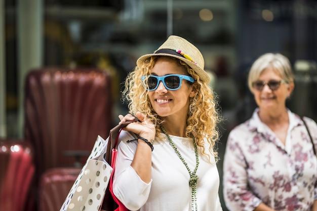 Duas mulheres caminhando juntas no centro comercial - vão às compras e gastam dinheiro com roupas - mãe e filha