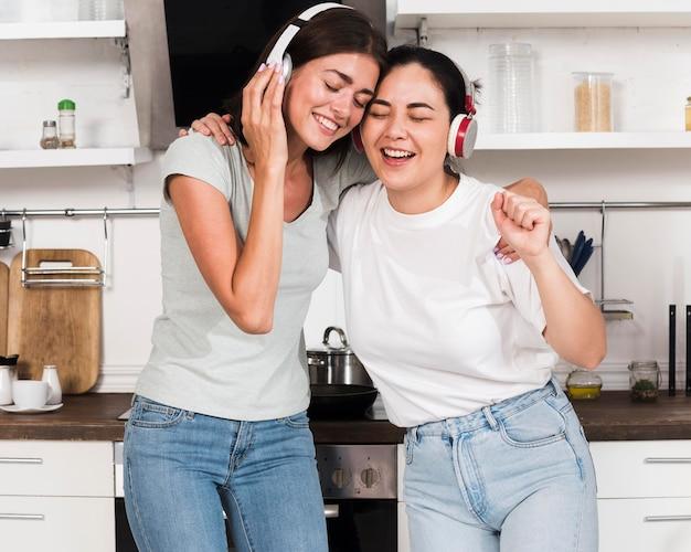 Duas mulheres cantando música em fones de ouvido