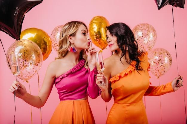 Duas mulheres com balões brilhantes conversando na festa