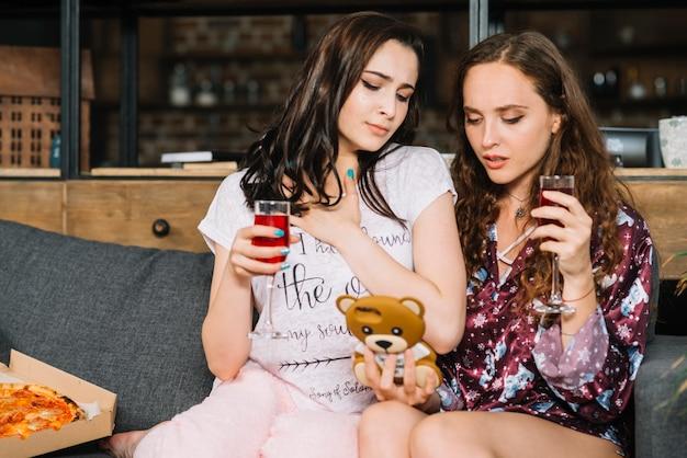 Duas mulheres, com, bebidas, olhar, cellphone
