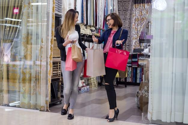 Duas mulheres, com, bolsas para compras, em, centro comercial