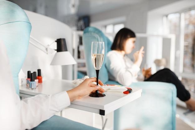 Duas mulheres com champanhe no salão de beleza. serviço profissional de esteticista, clientes do sexo feminino, tratamento de unha e unha no spa