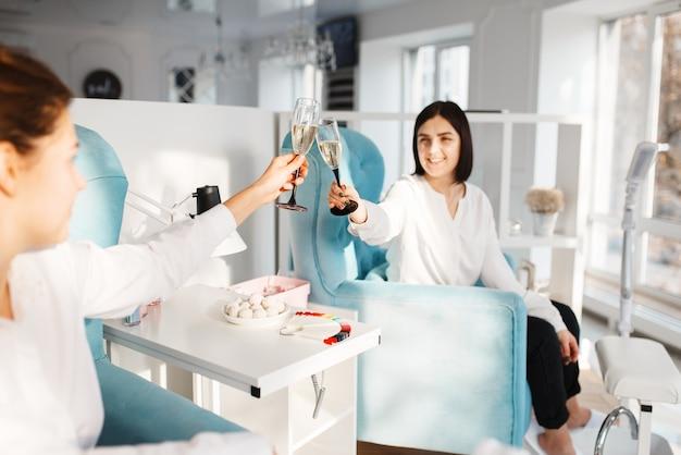 Duas mulheres com champanhe no salão de beleza. serviço profissional de esteticista, tratamento de unha e unha