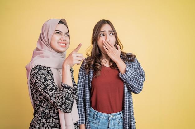 Duas mulheres com gesto de surpresa e apontando com copyspace