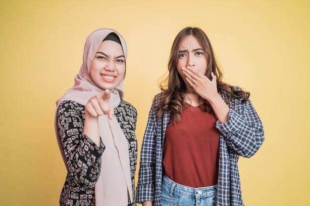 Duas mulheres com gestos surpresos e apontando