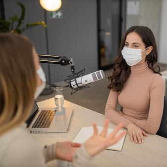 Duas mulheres com máscara médica conversando no rádio