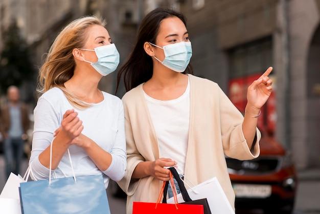 Duas mulheres com máscaras médicas e sacolas de compras em promoção