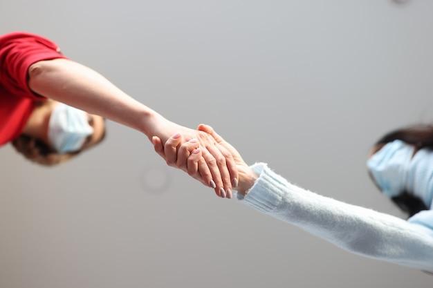 Duas mulheres com máscaras médicas protetoras apertam as mãos comunicação segura na pandemia de coronavírus
