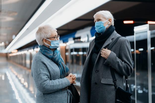 Duas mulheres com máscaras protetoras conversam em pé na plataforma do metrô