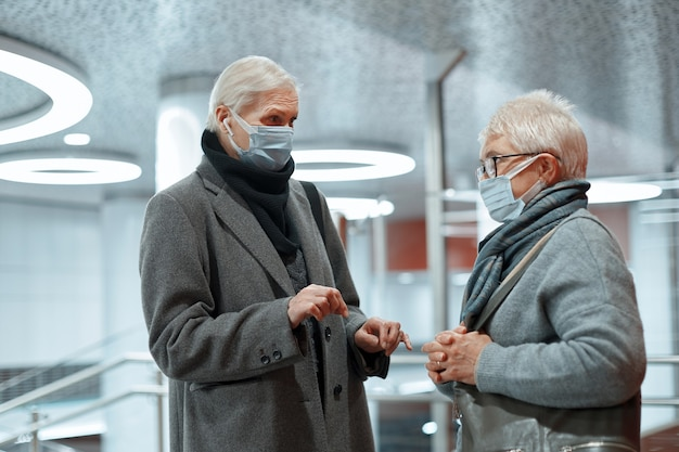 Duas mulheres com máscaras protetoras conversam em pé no prédio da estação