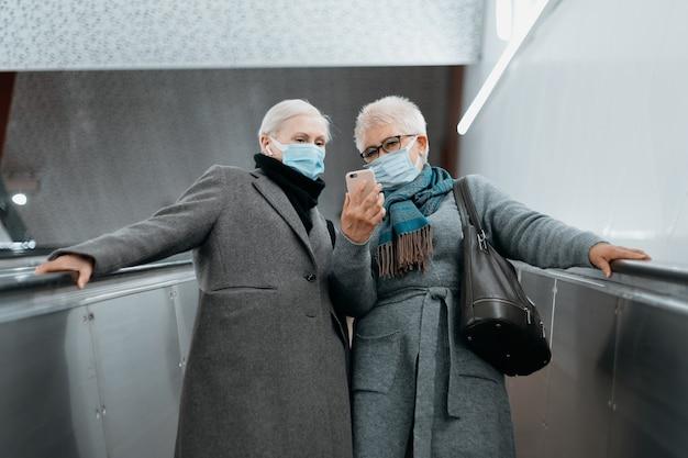 Duas mulheres com máscaras protetoras descendo para o metrô
